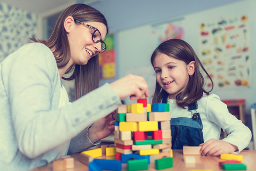teacher and young girl learning with multicolored wood building blocks