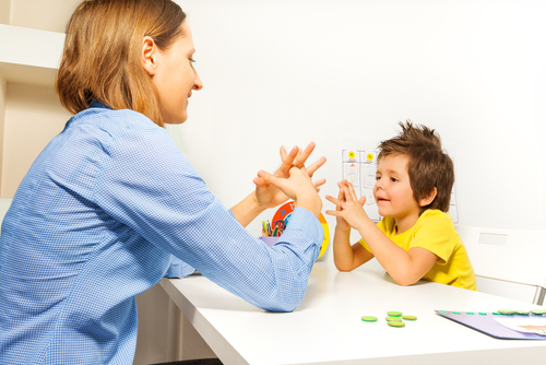 woman teaching young boy how to interlace his fingers