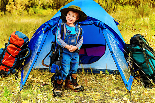smiling child in hiking gear standing outside of a tent