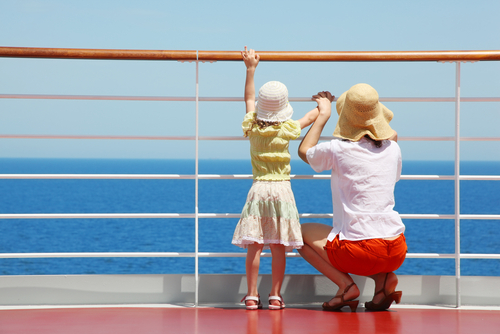 woman and young girl looking out at ocean through cruise ship railing