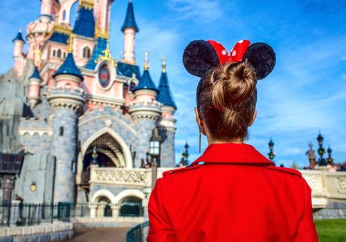 woman with mouse ear headband looking at Cinderella's castle