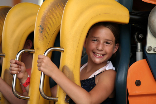 girl smiling in roller coaster seat