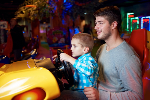 boy on man's lap behind the wheel of a driving video game