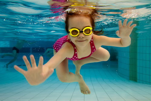 girl in goggles and polka dot swim suit swimming under water in a pool