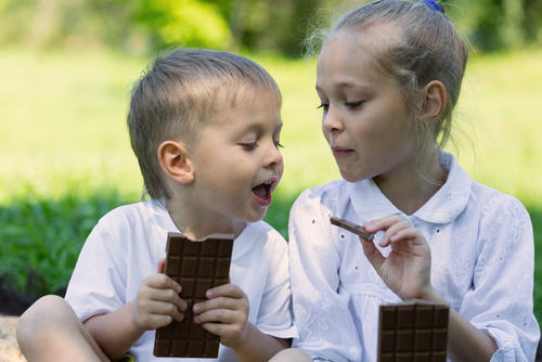 young girl and boy enjoying chocolate bars outdoors