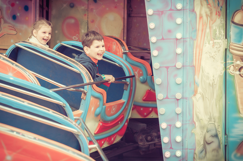 children laughing and smiling on carnival ride
