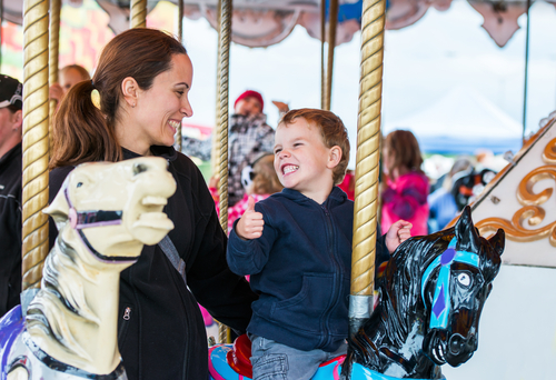 smiling boy riding a horse on a carousel and giving a thumbs up to adult woman