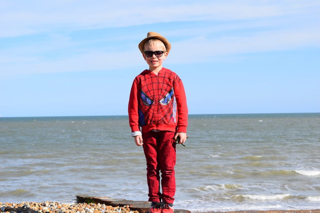 boy in spiderman hoodie with ocean in the background
