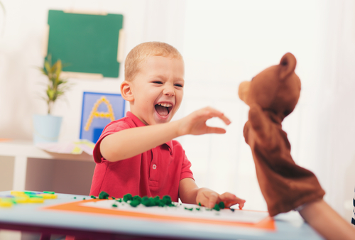 boy at desk interacting with teddy bear puppet