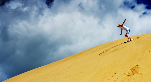 person sandboarding down large sand dune