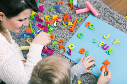 woman and child working with small foam letters and numbers