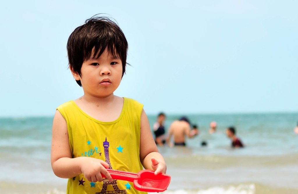 child on the beach with a plastic sand shovel