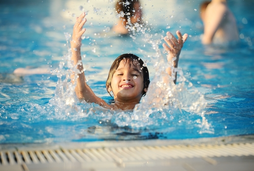 child smiling and splashing in a pool