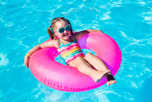 girl in sunglasses floating on a pink innertube in a pool