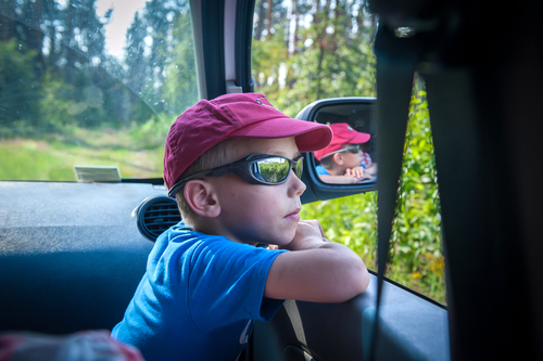 boy in hat and sunglasses enjoying the scenery from a car on a trail