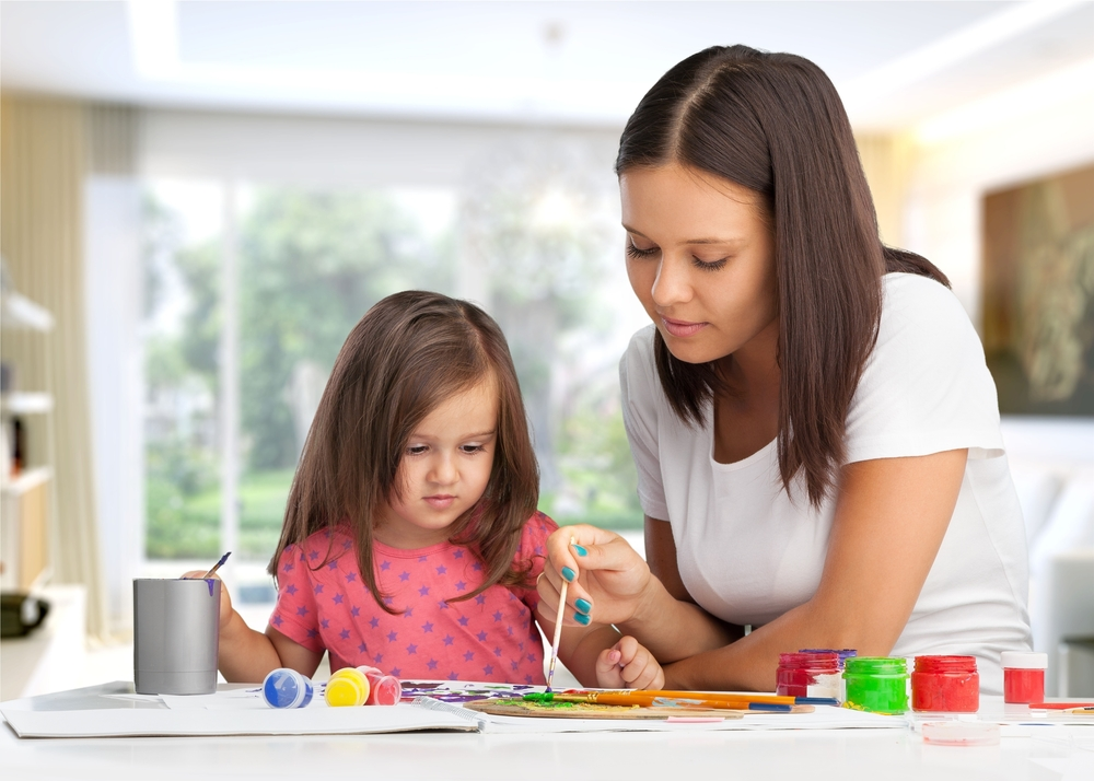 woman and young girl painting with bright colors
