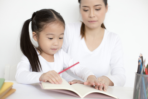young girl reading with adult